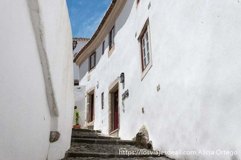 calle empedrada con casas blancas haciendo curva en pendiente
