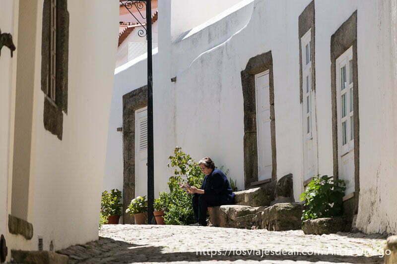 calle de marvao con casas blancas marcos de puerta de piedra y una señora leyendo al sol