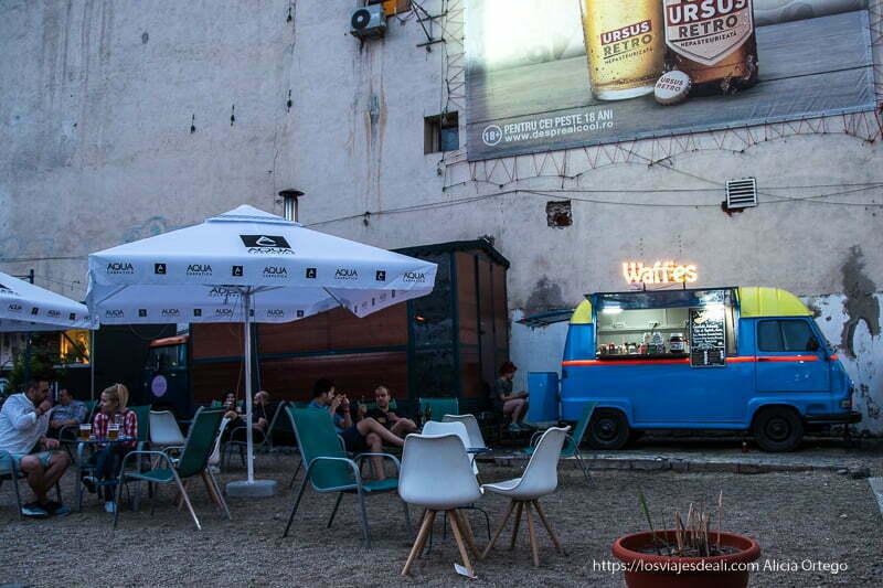 terraza con gente tomando cerveza y una furgoneta-bar en un patio del centro de bucarest