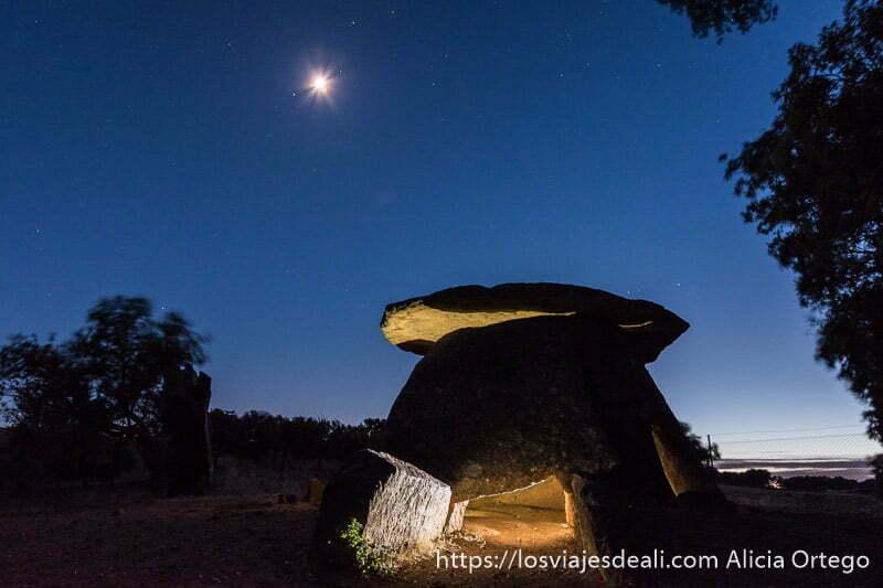dolmen iluminado por dentro con cielo muy azul y la luna brillando