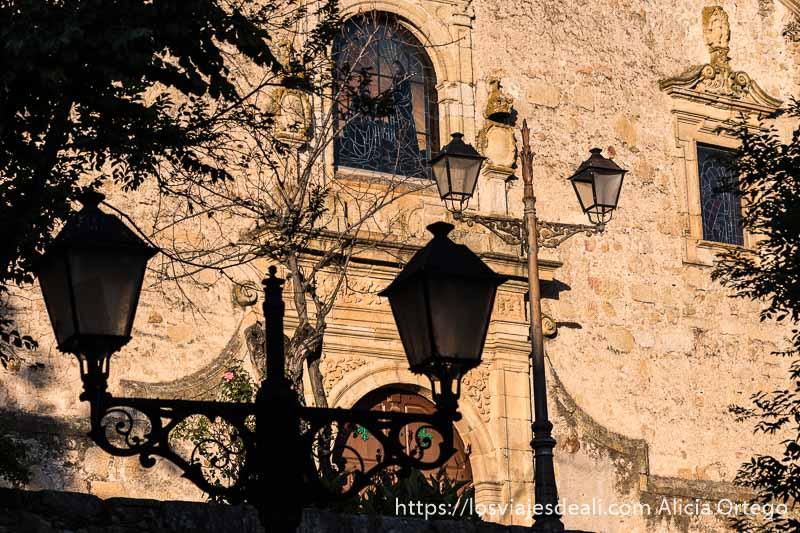 farolas y fachada de iglesia con luz dorada de atardecer en la escapada a cáceres