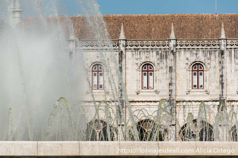 fuente con chorros de agua y al fondo la fachada del monasterio en belem