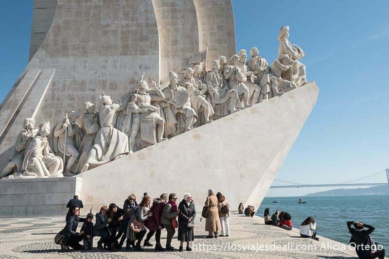 monumento a los descubridores de belem con un grupo de mujeres delante imitando la posición