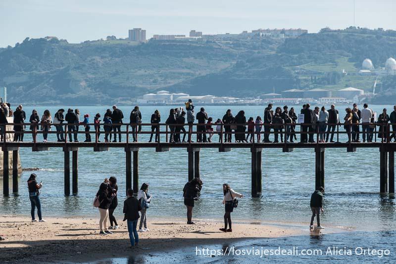 gente haciendo cola en la pasarela de madera que da acceso a la torre de belem