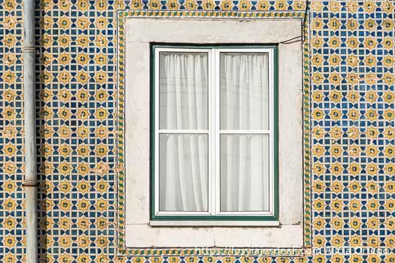 fachada de azulejos con formas geométricas y una ventana en el centro en belem