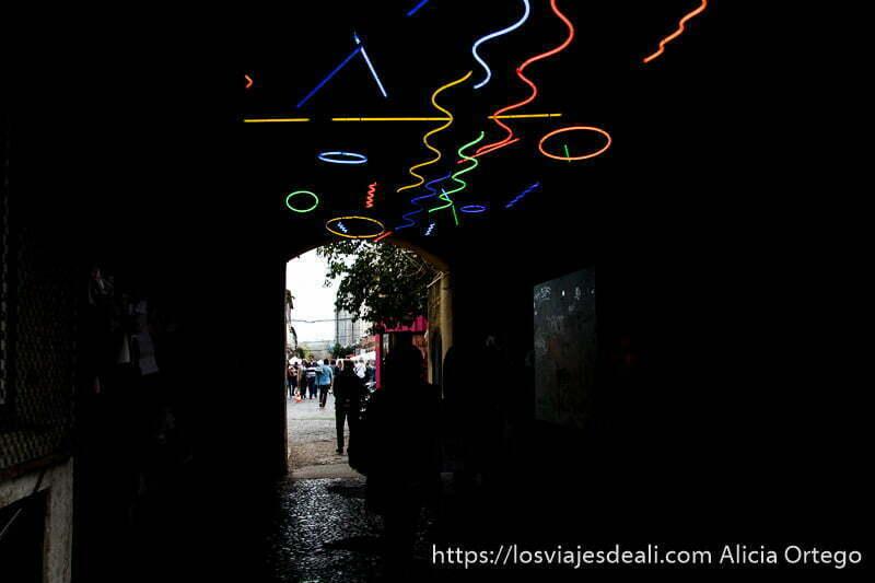 pasillo de entrada a factoría x con fluorescentes de colores haciendo formas onduladas