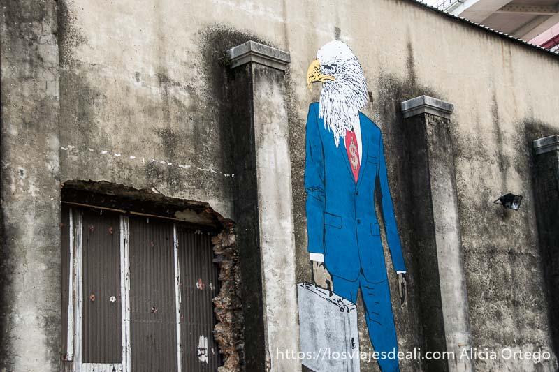 dibujo en un muro de un hombre con traje y símbolo del dólar en corbata y cabeza de águila