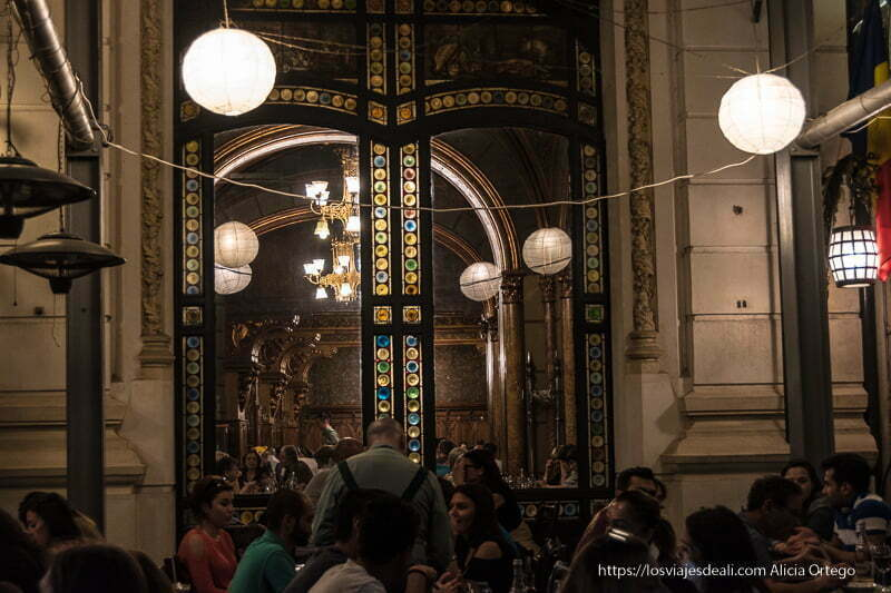 restaurante en edificio histórico como un antiguo café clásico con lámparas en forma de bola y grandes columnas
