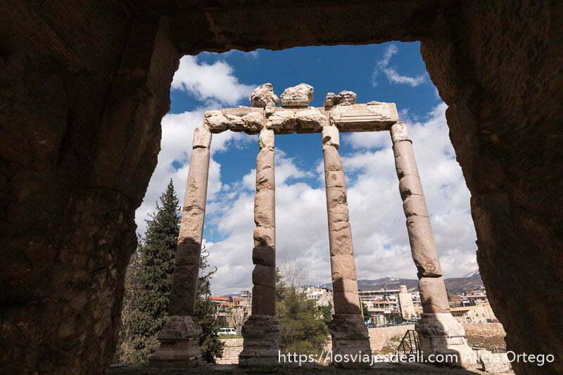 friso sostenido por cuatro grandes columnas enmarcado en puerta de piedra en las ruinas de baalbek