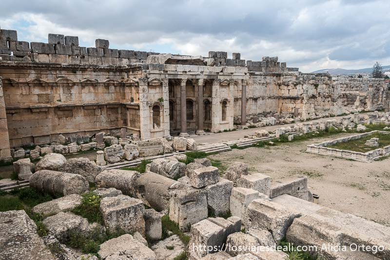 fachada de un gran templo de baalbek con nichos para estatuas y grandes columnas sosteniendo techo