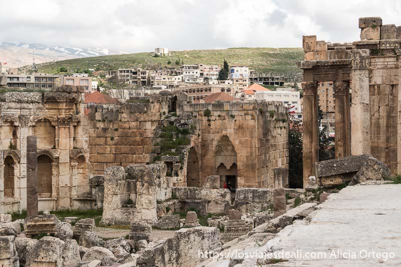 vista de muros y columnas con monte verde al fondo y parte de la ciudad de baalbek