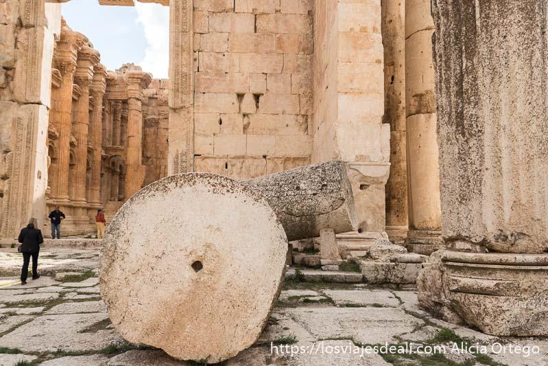 grandes columnas caídas con agujero en el centro y detrás la puerta al interior del templo de Baco en baalbek
