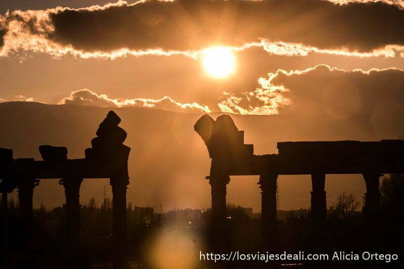 puesta de sol con pórtico sostenido por columnas a contraluz en baalbek