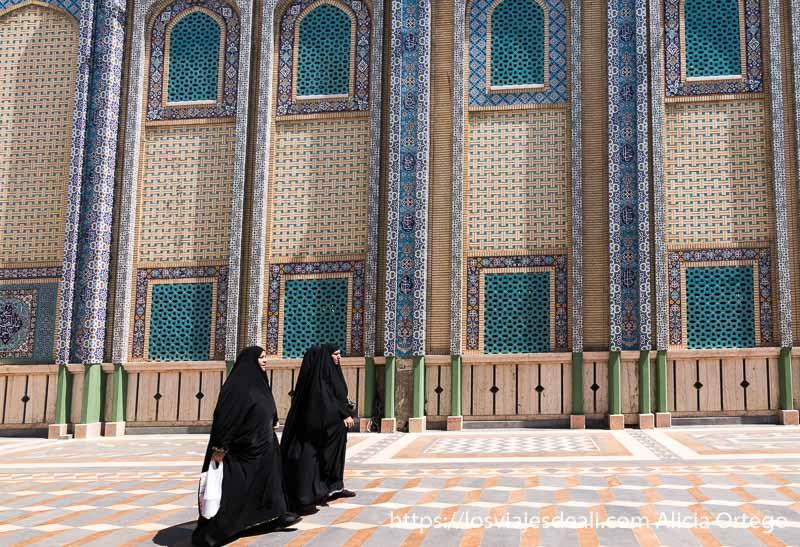 tres mujeres con chador negro pasan delante de la mezquita chií de baalbek en el valle de bekaa