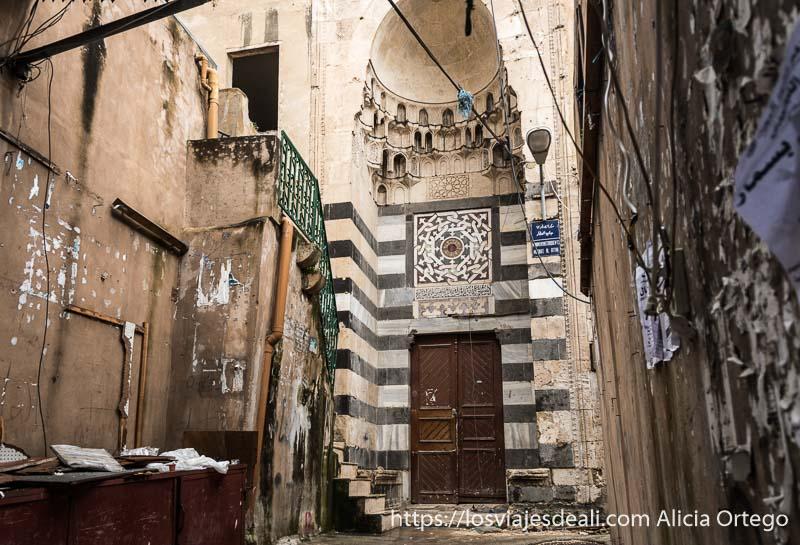 puerta de mezquita otomana con fachada a rayas de mármol oscuro y claro