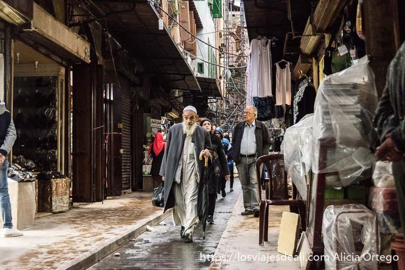 calle del zoco de trípoli con hombre musulmán de barba blanca, gafas y gorrito blanco andando de frente