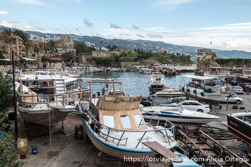 puerto de byblos con torre de piedra antigua a la derecha y barcos de recreo en dique seco