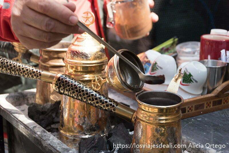 cafeteras de cobre sobre brasas y una mano echando café en una de ellas en byblos