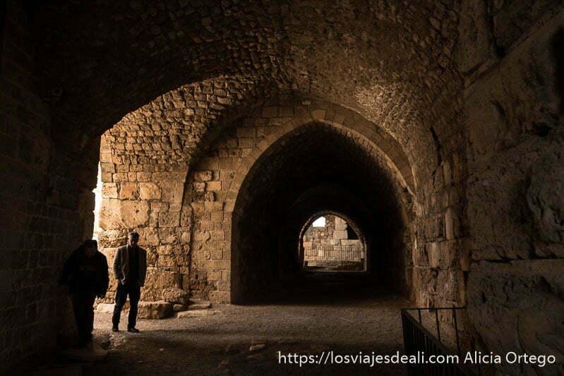 galería con bóvedas todo de piedra y un hombre entrando desde el patio en el castillo de los cruzados de byblos