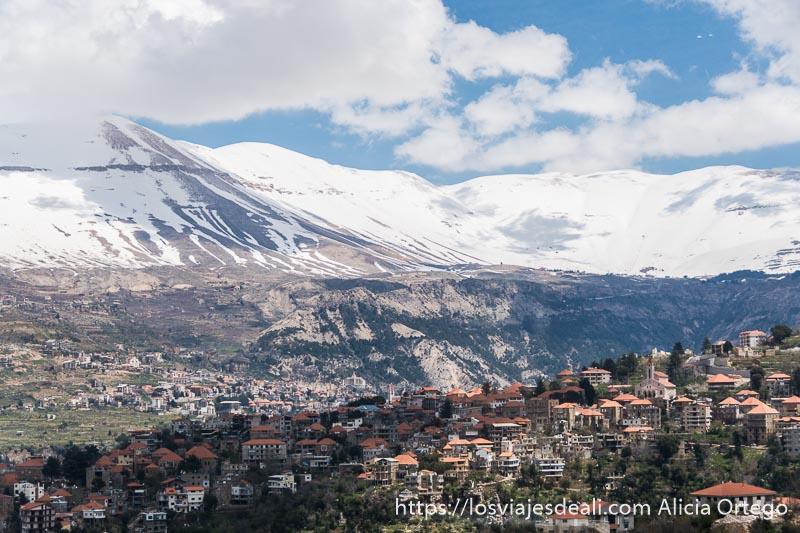 pueblo maronita lleno de casas con tejados rojos y montañas con nieve