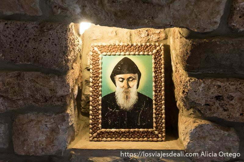 retrato del santo de los maronitas iluminado con una bombilla en un hueco de pared de piedra en el monasterior