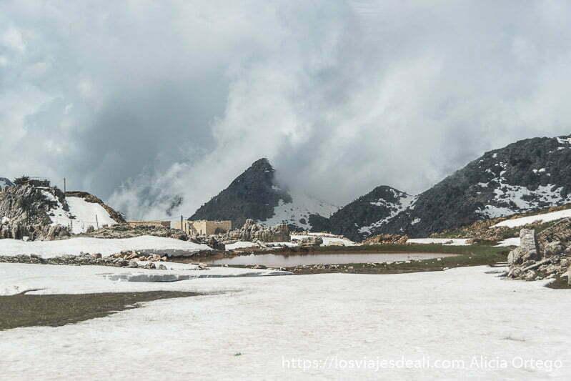campo nevado con montañas al fondo medio cubiertas por nubes de tormenta