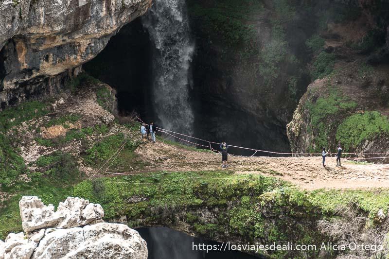 cascada 3 points con gente andando sobre un arco de roca caliza y el agua cayendo hacia una sima profunda