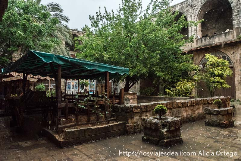 patio de caravanserai con gran fuente en el centro y dos pisos con arcos y árboles en el centro de trípoli