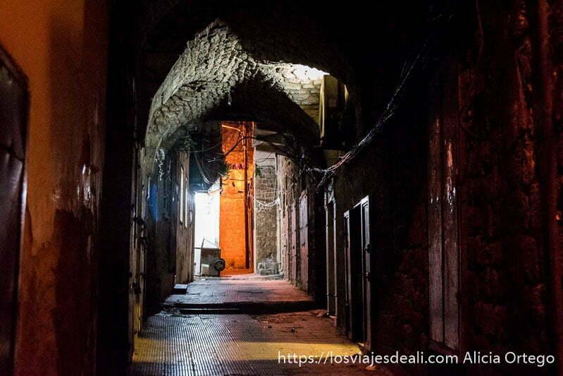 calle oscura con luces que salen de los locales y bóveda de ladrillo en trípoli