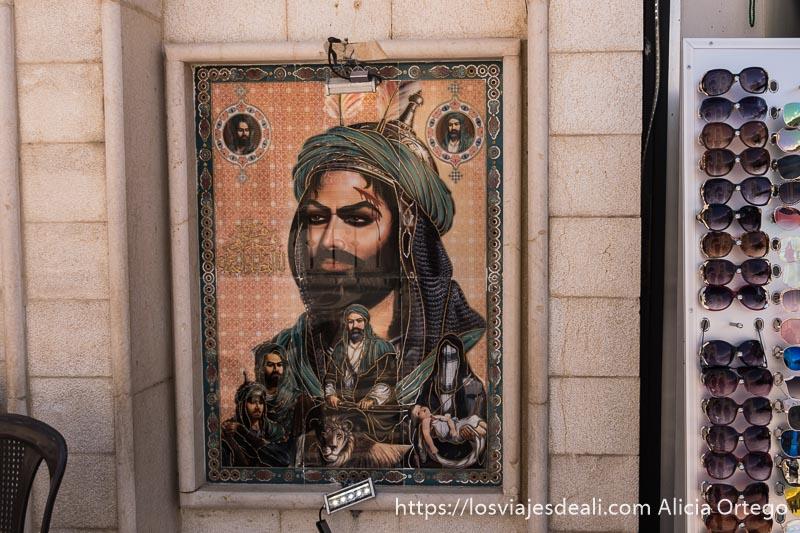 cuadro de azulejos en la pared con rostro del imam hussein y debajo otros hombres un león y una mujer con niña muerta en sus brazos