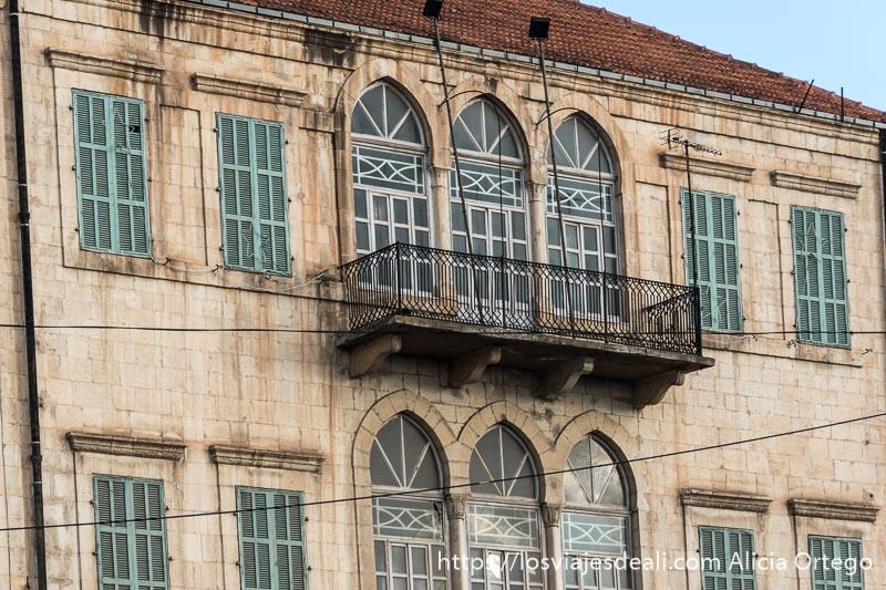 fachada de casa antigua de piedra con balcón de hierro y ventanas de color verde en baalbek