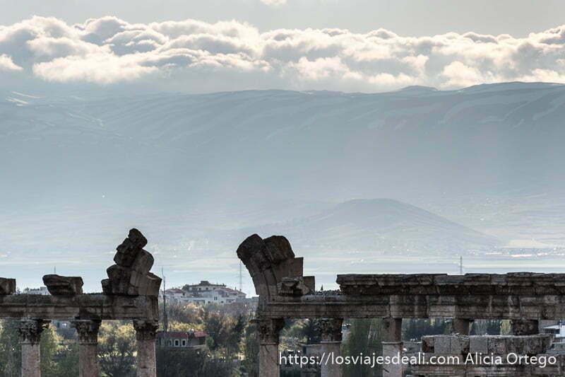 columnas y arco roto con montañas al fondo y nubes en baalbek