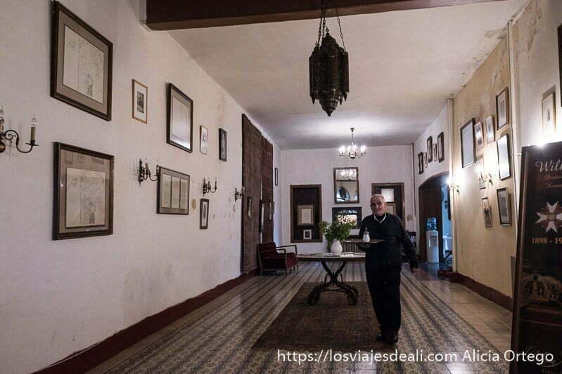 pasillo del hotel palmyra lleno de fotos antiguas y un camarero mayor viniendo con bandeja en la mano