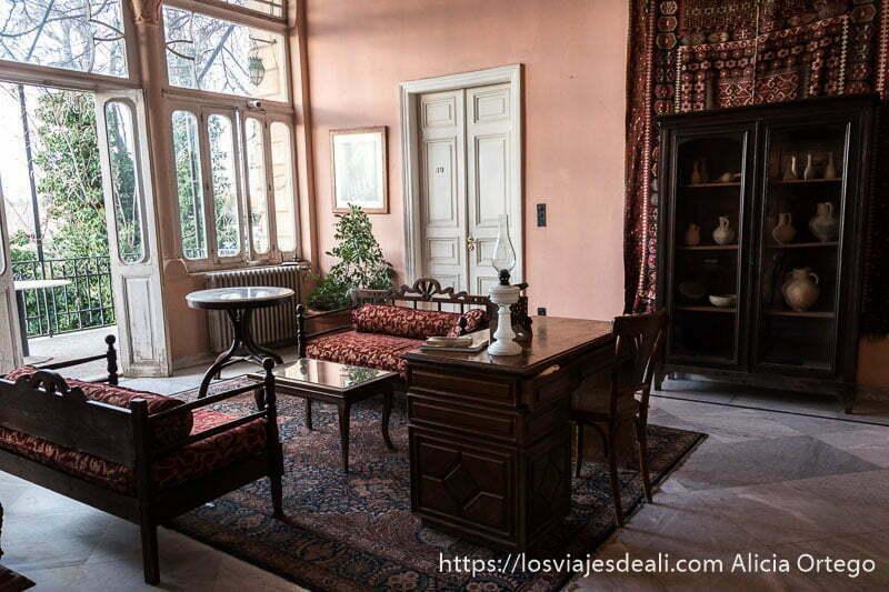 salón con balcón y muebles de madera con sofás de tipo oriental en el hotel palmyra de baalbek