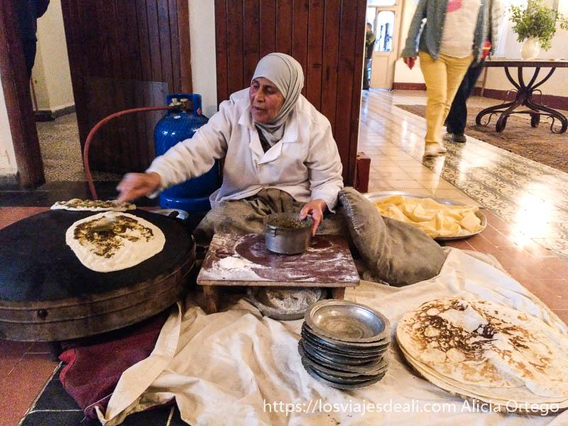 mujer haciendo pan en horno circular y poniendo mezcla de hierbas y aceite para desayunar en el hotel palmyra