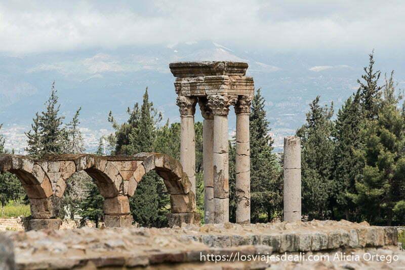 tetrapilón con arcos al lado y árboles al fondo en las ruinas de aanjar