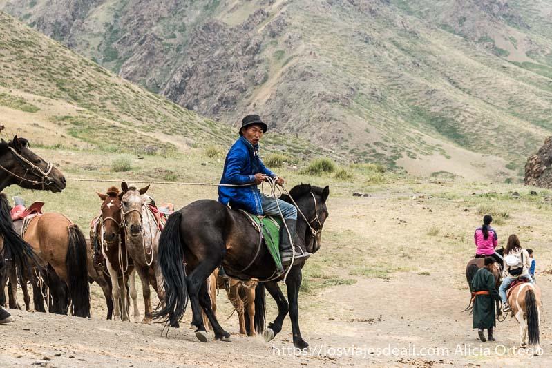 hombre mongol sobre su caballo tirando de las riendas de otro