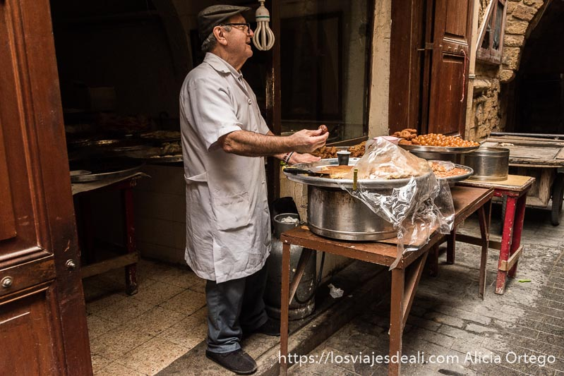 simpático vendedor del zoco de sidón ofreciendo dulces a la gente que pasa delante de su tienda viajar a líbano
