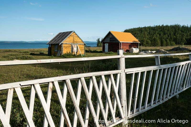 dos casitas de madera con tejado a dos aguas pintadas de colores y una valla de madera blanca y un lago detrás en el viaje a mongolia