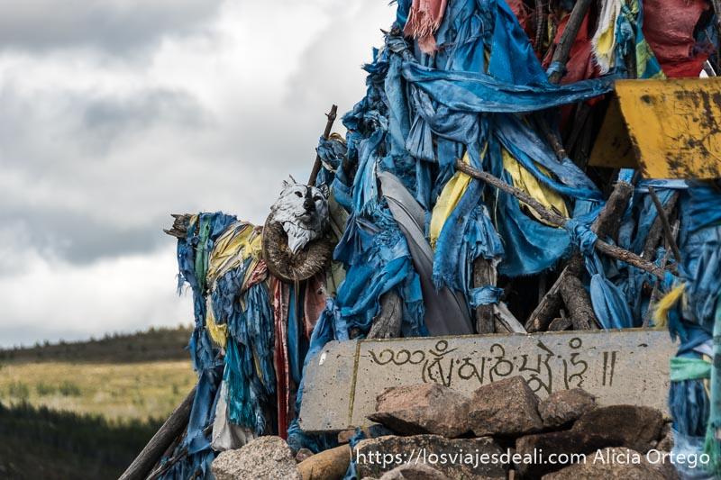 altar cubierto de pañuelos azules y amarillos en la montaña en el viaje a mongolia