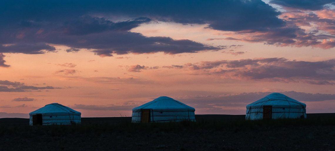 tres gers se recortan en el horizonte con colores y nubes de atardecer en el viaje a mongolia