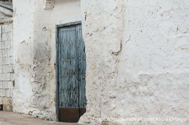 puerta de madera de color azul entre paredes blancas durante la experiencia en la vendimia