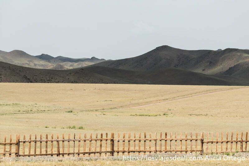 paisaje con una valla de madera y detrás montañas oscuras en el desierto del gobi