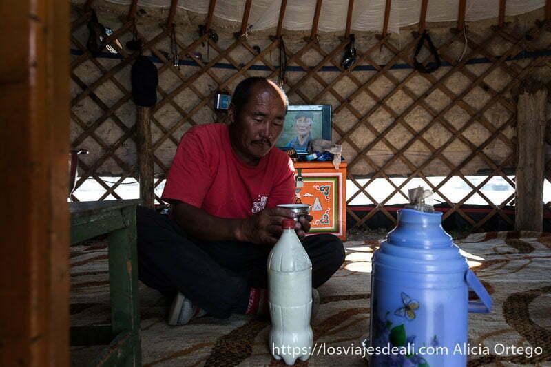 anfitrión mongol en su get con la tele detrás encendida y termos de té con leche