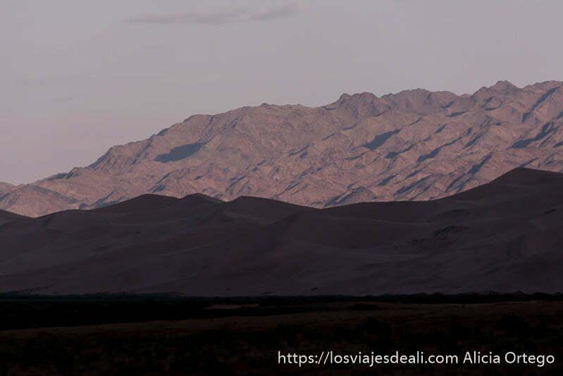 paisaje de montañas peladas y dunas en primer plano en sombra al atardecer viajar a mongolia
