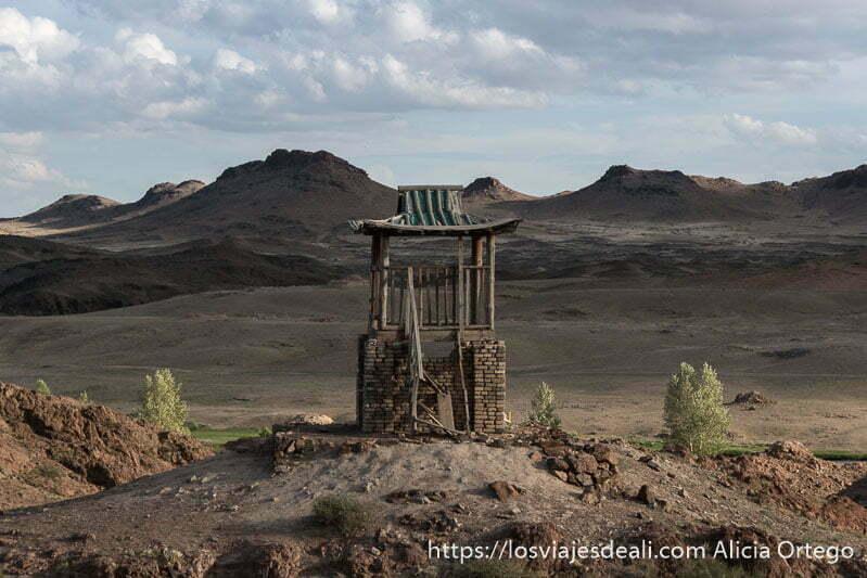 torre del antiguo monasterio de ongii con montañas volcánicas al fondo en el desierto del gobi
