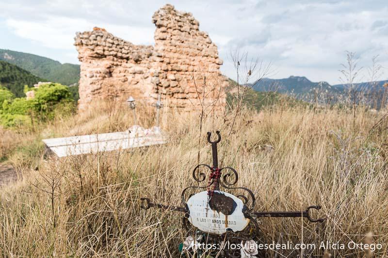 tumbas entre hierbas altas secas y un torreón de la muralla de riopar viejo en albacete