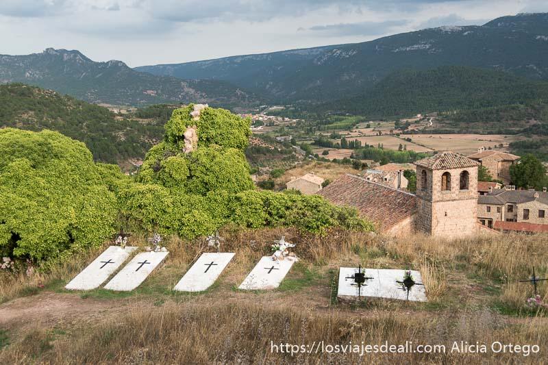 tumbas pintadas de blanco mirando al pueblo que se extiende más abajo y el valle al fondo