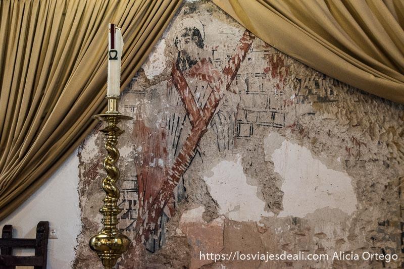 pintura al fresco de un santo en colores negros y rojos en la iglesia de riópar viejo