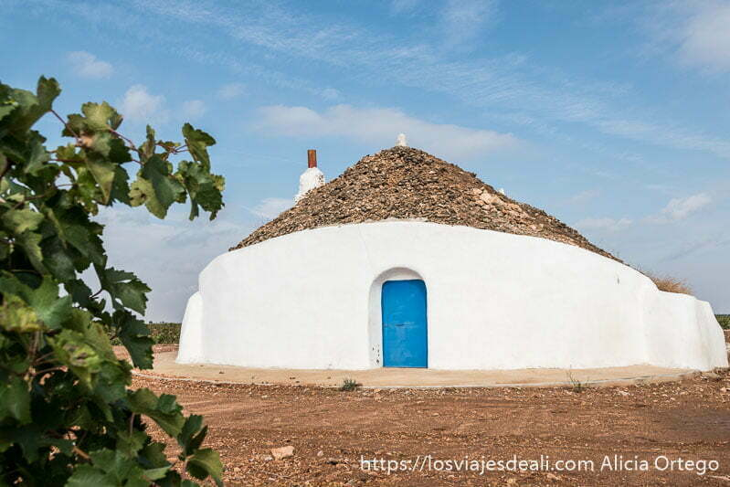 bombo manchego en el campo con paredes encaladas y puerta pintada de añil con cielo azul